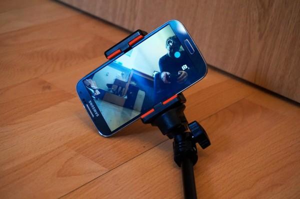 Das Smartphone wird in die Klemmen des Selfie-Sticks geklemmt.